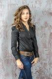 Chica joven con el pelo rizado en una camisa negra, vaqueros y un estilo occidental del alto vaquero de las botas Imagenes de archivo