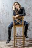 Chica joven con el pelo rizado en una camisa negra, vaqueros y un estilo occidental del alto vaquero de las botas Fotos de archivo