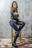 Chica joven con el pelo rizado en una camisa negra, vaqueros y un estilo occidental del alto vaquero de las botas Imágenes de archivo libres de regalías