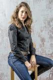 Chica joven con el pelo rizado en una camisa negra, vaqueros y un estilo occidental del alto vaquero de las botas Fotos de archivo libres de regalías