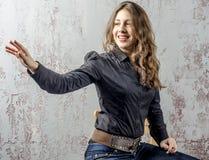 Chica joven con el pelo rizado en una camisa negra, vaqueros y un estilo occidental del alto vaquero de las botas Fotografía de archivo libre de regalías