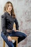 Chica joven con el pelo rizado en una camisa negra, vaqueros y un estilo occidental del alto vaquero de las botas Foto de archivo