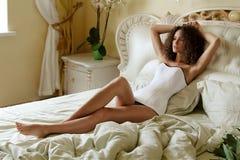Chica joven con el pelo rizado que miente en una cama con la cama desgreñada en un corsé blanco y miradas en la distancia en el b fotografía de archivo libre de regalías