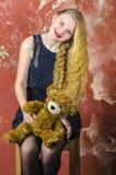 Chica joven con el pelo rizado rubio en un vestido largo con los lunares con el oso de peluche Imagenes de archivo