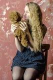 Chica joven con el pelo rizado rubio en un vestido largo con los lunares con el oso de peluche Imagen de archivo libre de regalías