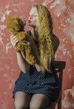 Chica joven con el pelo rizado rubio en un vestido largo con los lunares con el oso de peluche Foto de archivo