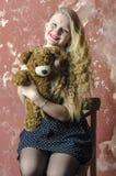 Chica joven con el pelo rizado rubio en un vestido largo con los lunares con el oso de peluche Fotografía de archivo libre de regalías