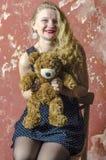 Chica joven con el pelo rizado rubio en un vestido largo con los lunares con el oso de peluche Fotos de archivo