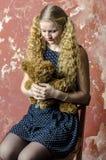 Chica joven con el pelo rizado rubio en un vestido largo con los lunares con el oso de peluche Imagen de archivo