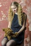 Chica joven con el pelo rizado rubio en un vestido largo con los lunares con el oso de peluche Fotografía de archivo