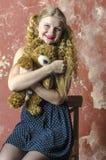 Chica joven con el pelo rizado rubio en un vestido largo con los lunares con el oso de peluche Imágenes de archivo libres de regalías