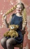 Chica joven con el pelo rizado rubio en un vestido largo con los lunares con el oso de peluche Fotos de archivo libres de regalías