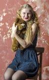 Chica joven con el pelo rizado rubio en un vestido largo con los lunares con el oso de peluche Foto de archivo libre de regalías