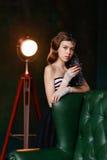 Chica joven con el pelo rizado y una boa de la piel que se coloca con un vidrio i imagenes de archivo
