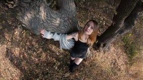 Chica joven con el pelo rojo en el bosque cerca del árbol Foto de archivo