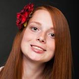 Chica joven con el pelo rojo que fluye en un fondo negro Imagen de archivo