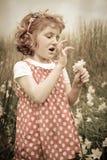Chica joven con el pelo rojo rizado en el campo de wildflowers imagen de archivo