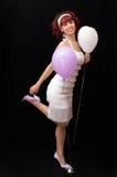Chica joven con el pelo y los globos rojos Foto de archivo