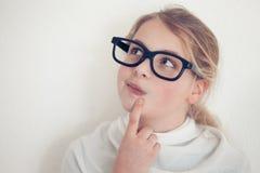 Chica joven con el pensamiento de los vidrios Foto de archivo libre de regalías