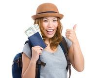 Chica joven con el pulgar ascendente y que sostiene el pasaporte con el dinero Imagenes de archivo