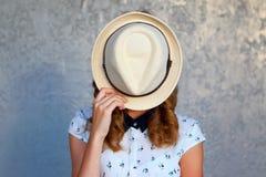 Chica joven con el sombrero Oculta su cara depresión Imagenes de archivo