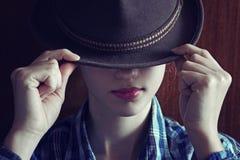 Chica joven con el sombrero Oculta su cara depresión Foto teñida Imagenes de archivo