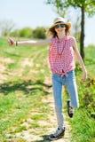 Chica joven con el sunhat que hace autostop encendido del camino imagen de archivo libre de regalías