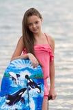 Chica joven con el tablero que practica surf Foto de archivo