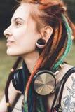 Chica joven con el tatuaje y dreadlocks que escuchan la música en el parque foto de archivo libre de regalías