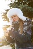 Chica joven con el teléfono celular en invierno Fotos de archivo libres de regalías