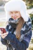 Chica joven con el teléfono celular en invierno Imagen de archivo