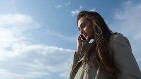 Chica joven con el teléfono contra el cielo azul almacen de video