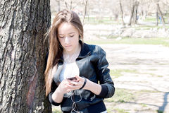 Chica joven con el teléfono elegante que se inclina en el árbol grande viejo Imágenes de archivo libres de regalías