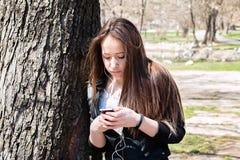 Chica joven con el teléfono elegante que se inclina en el árbol grande viejo Imagen de archivo