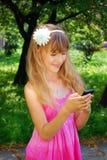 Chica joven con el teléfono móvil en parque Imágenes de archivo libres de regalías