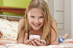 Chica joven con el teléfono móvil, sonriendo Foto de archivo