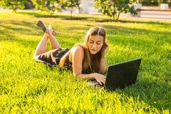 Chica joven con el trabajo del ordenador portátil al aire libre Foto de archivo libre de regalías