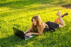 Chica joven con el trabajo del ordenador portátil al aire libre Imagen de archivo libre de regalías