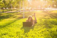 Chica joven con el trabajo del ordenador portátil al aire libre Imagenes de archivo
