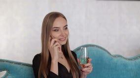 Chica joven con el vidrio de champán que habla en el teléfono en el partido metrajes