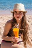 Chica joven con el vidrio de jugo que se sienta en la playa Fotografía de archivo