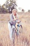 Chica joven con la bici en el campo Foto de archivo