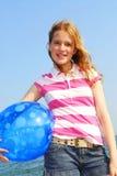 Chica joven con la bola de playa Imagenes de archivo