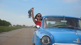Chica joven con la bufanda a disposición que se inclina fuera de la ventanilla del coche del vintage y que disfruta de viaje La m almacen de metraje de vídeo