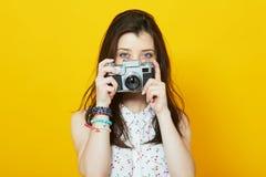 Chica joven con la cámara del vintage sobre fondo amarillo Imagenes de archivo