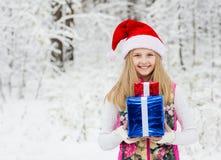 Chica joven con la caja de regalo en bosque del invierno Imagenes de archivo