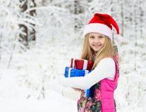 Chica joven con la caja de regalo y el sombrero de santa en bosque del invierno Imagen de archivo libre de regalías