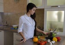 Chica joven con la cocina del artilugio Imagenes de archivo
