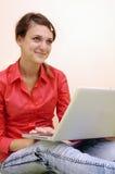 Chica joven con la computadora portátil foto de archivo