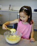 Chica joven con la cuchara de la mezcla de la torta. Fotos de archivo libres de regalías